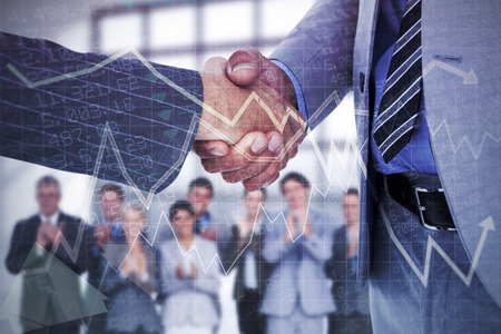 co: Businessman shaking hands with a co worker against stocks and shares Stock Photo