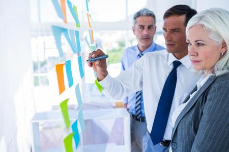 reuniones empresariales: El hombre de negocios por escrito en el post-it con sus colegas en la oficina Foto de archivo