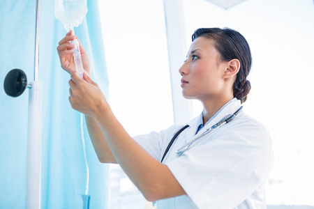 an intravenous drip: Concentrated female doctor connecting an intravenous drip in hospital Stock Photo