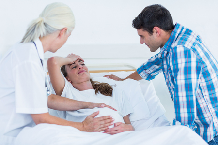 mid adult women: Pregnant woman and her husband having a doctor visit in hospital