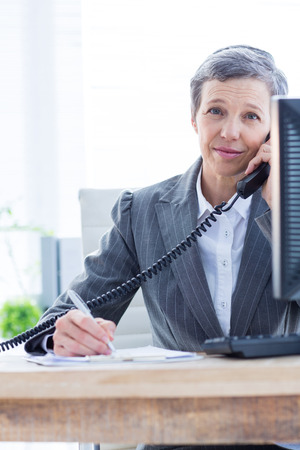 phoning: Smiling portrait of a businesswoman phoning and writing at the office Stock Photo