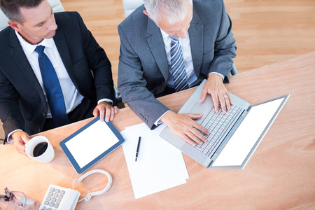 mature business man: High view of businessmen working together on laptop in the office