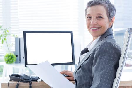 usando computadora: Empresaria sonriente que usa el ordenador en la oficina Foto de archivo