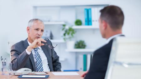 empresario: Dos hombres de negocios serios hablando y trabajando en la oficina