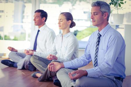 Business people doing yoga on floor in office Foto de archivo