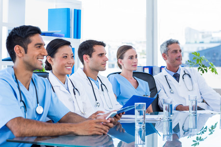 Doctors listening while sitting at a table in medical office
