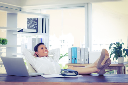 calm woman: Businesswoman relaxing in a swivel chair in office