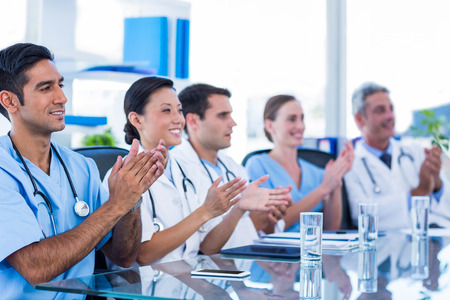 applauding: Doctors applauding while sitting at a table in medical office Stock Photo
