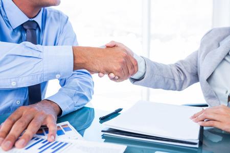 dando la mano: La gente de negocios dándose la mano en la oficina