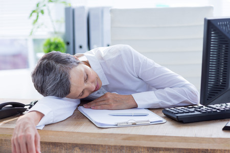 tired businessman: Tired businessman sleeping at her desk on the office Stock Photo