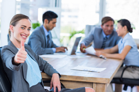 thumbs up: Business people speaking together during meeting in office