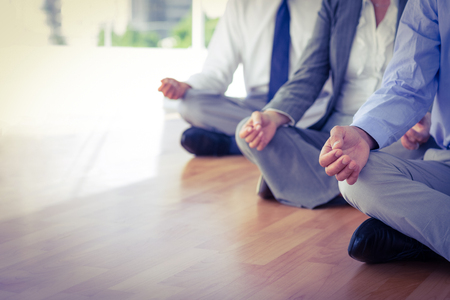 mujer meditando: Cierre de vista de la gente de negocios que hace yoga en la oficina Foto de archivo