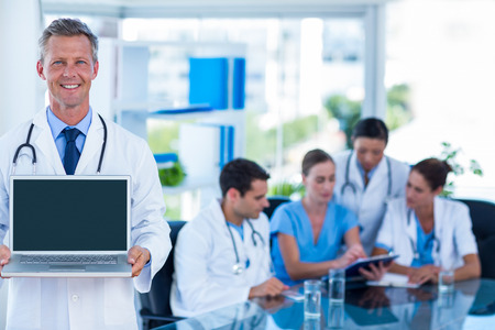medical team: Doctor showing laptop with colleagues behind in medical office
