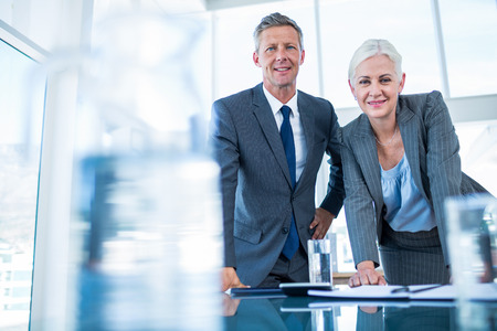 glass paper: Business people looking at camera behind desk in office Stock Photo