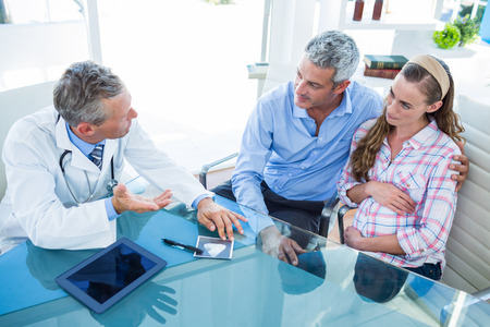 mid adult women: Pregnant woman and her husband discussing with doctor in clinic Stock Photo