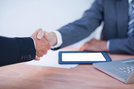 dando la mano: Dos colegas empresarios estrechar la mano en la oficina