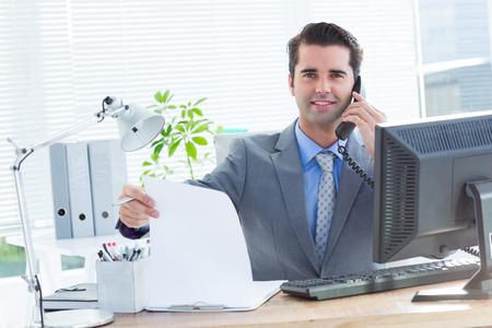 persona llamando: Retrato de un hombre de negocios profesional de cheques en su cuaderno mientras habla por teléfono