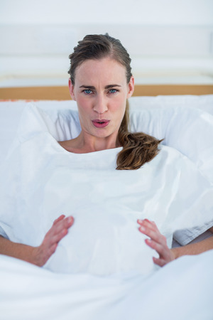 pains: Portrait of pregnant woman suffering from labor pains lying in bed at hospital