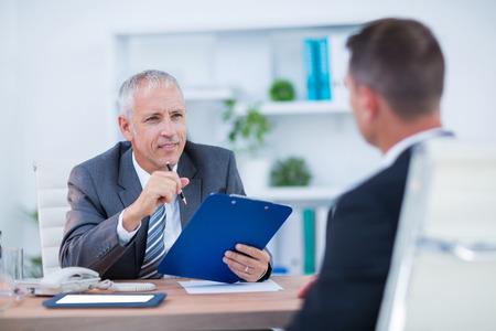 ejecutivo en oficina: Dos hombres de negocios que se sientan y hablan y trabajan en la oficina