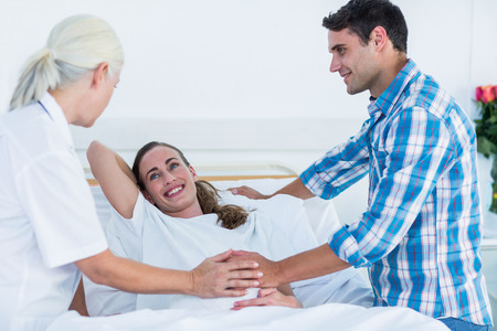 pregnant mom: Pregnant woman and her husband having a doctor visit in hospital