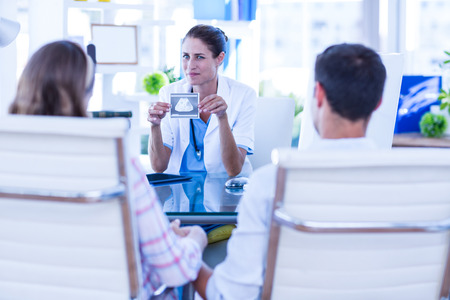 obstetrician: Doctor showing sonagram to couple in office at the hospital Stock Photo