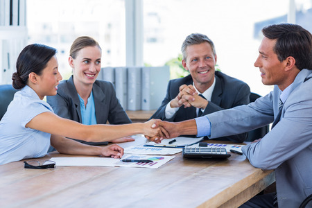 shaking: Business people shaking hands during meeting in office