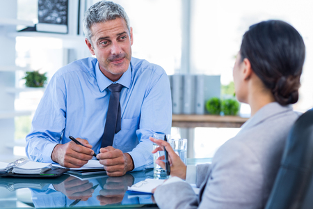 deals: Happy business people shaking hands in office Stock Photo