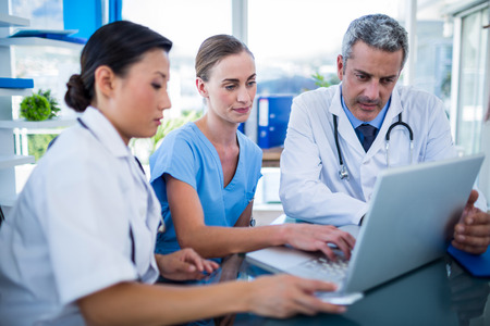 medical doctors: Doctors and nurse looking at laptop in medical office Stock Photo