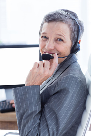 phoning: Smiling businesswoman phoning and using computer at the office Stock Photo
