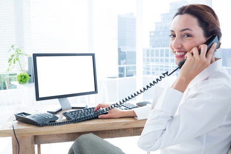phoning: Smiling businesswoman using computer and phoning at the office