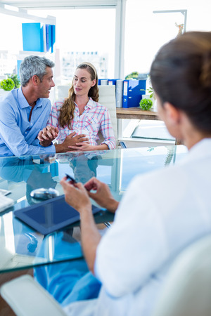 gynaecologist: Pregnant woman and her husband discussing with doctor in clinic Stock Photo