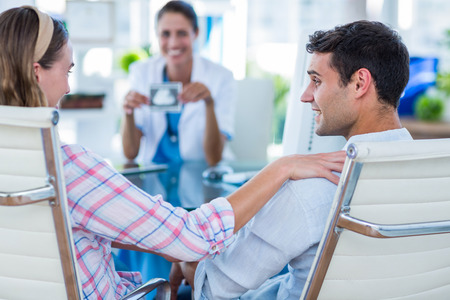 examination room: Rear view of pregnant woman and her husband discussing with doctor in an examination room Stock Photo