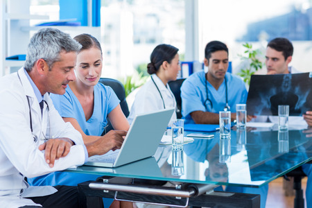 Doctor and nurse looking at laptop with colleagues behind in medical office Stockfoto