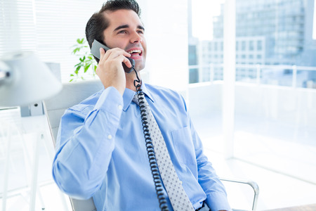 Smiling businessman phoning on his office