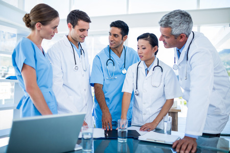 Doctors and nurses discussing together in medical office
