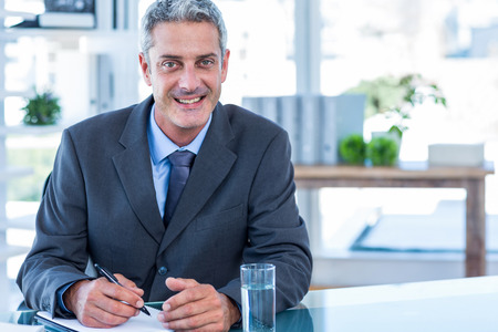 middleaged: Happy businessman looking at camera in office Stock Photo