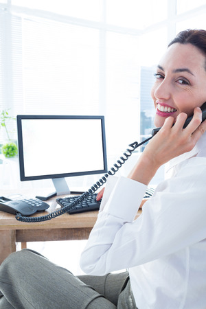 Smiling businesswoman using computer and phoning at the office
