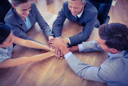 joining hands: Business people joining hands in a circle in the office Stock Photo