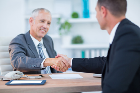man arm: Happy businessmen shaking hands in the office