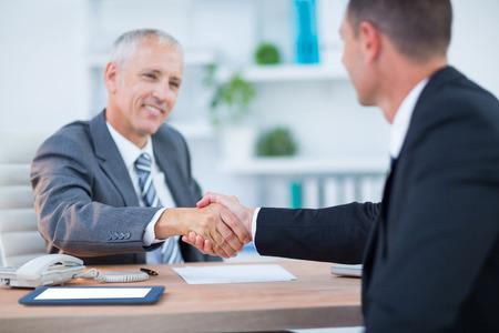 dando la mano: Hombres de negocios felices agitando las manos en la oficina