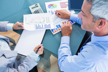 business graphics: Business people looking at documents with graphics in office
