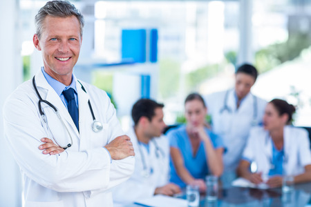 medical office: Doctor smiling at camera with colleagues behind in medical office Stock Photo