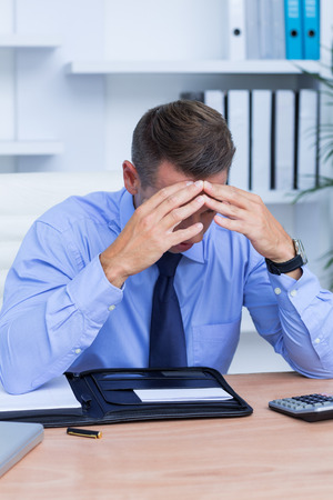 pounding head: Elegant businessman with severe headache sitting at office desk