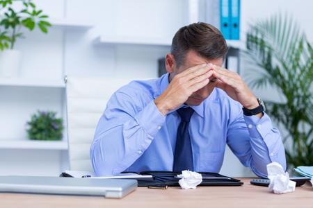 male headache: Elegant businessman with severe headache sitting at office desk