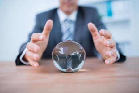 Zakenman voorspellen een kristallen bol in het kantoor