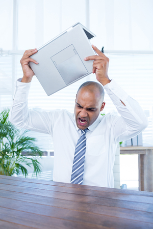irritated: Irritated businessman about to break his laptop at office Stock Photo