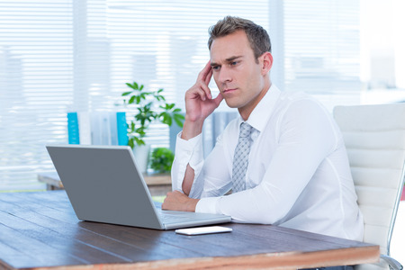 frowning: Frowning businessman looking at his laptop at office