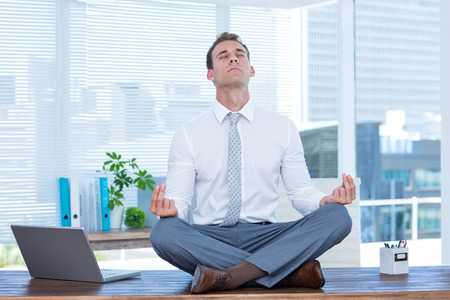 workplace wellness: Zen businessman doing yoga meditation on the desk Stock Photo