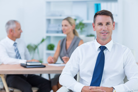 mid adult men: Happy businessman smiling at camera with colleagues behind in the office Stock Photo