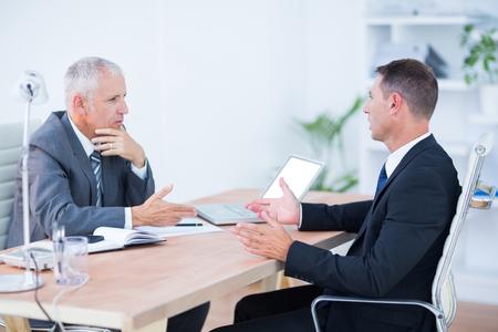 personas dialogando: Dos hombres de negocios serios hablando y trabajando en la oficina